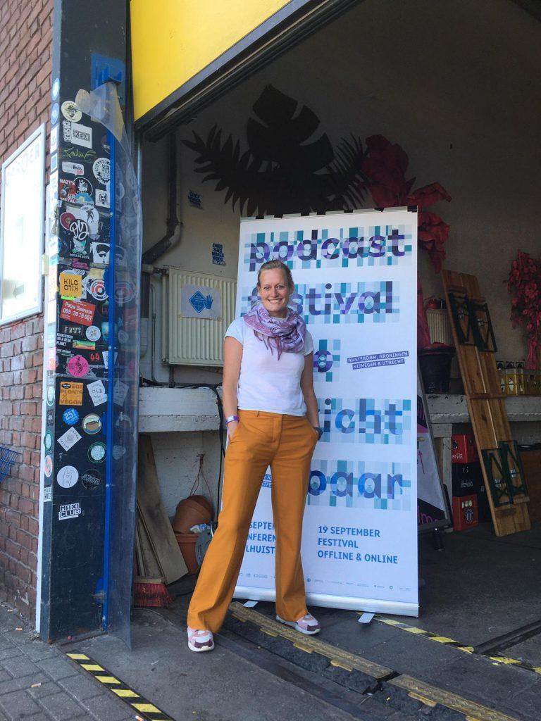Pitchwedstrijd winnaar Marieke de Veer staat voor de podcastfestival banner