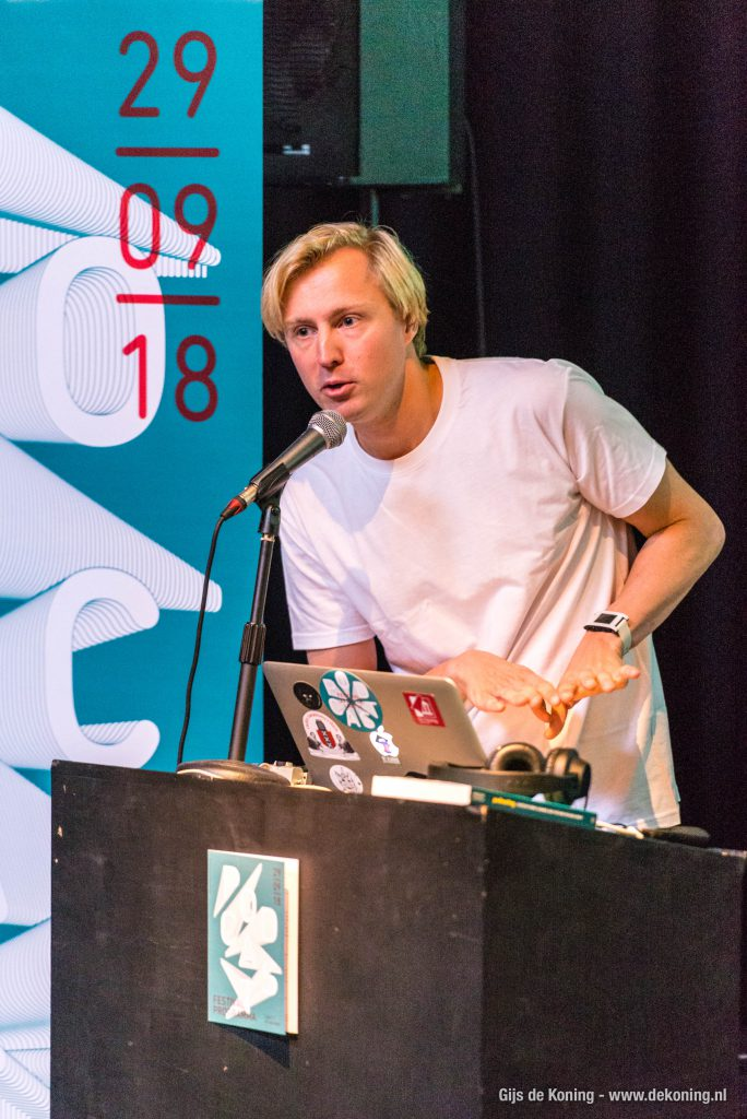 Lieven praat in een microfoon achter een spreekgestoelte. Achter hem een blauwe banner met de podcastfestival 2018 datum er op, voor hem zijn laptop en een koptelefoon