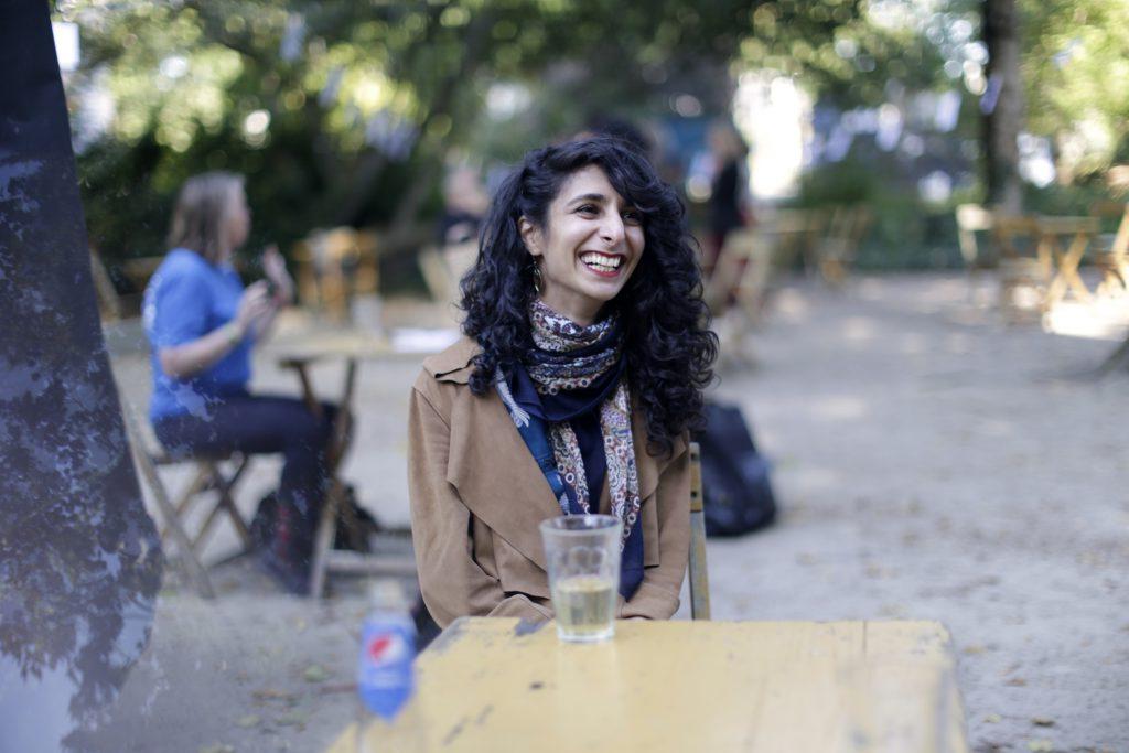 Mina zit in de tuin van de tolhuistuin aan een tafel en lacht heel leuk. Ze heeft lange donkere krullen en een sjahwltje om