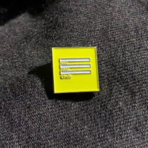 vierkante emaillen pin met daarop podcastclub, de achtergrond is zwarte jeans